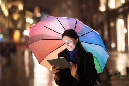 people: Happy young girl with colorful umbrella using tablet computer outdoor. She standing in the city street in the rainy evening