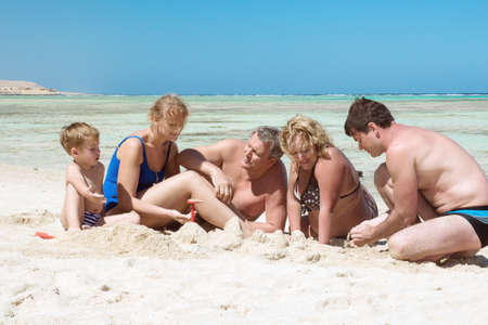 sand castle: Members of a big family are sitting by the sea and building sand castle.