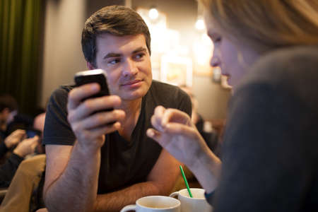 look pleased: Young man using cellphone during the meeting with a girl in a cafe, but his look is attracted by someone else Stock Photo