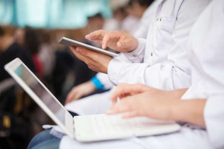 Male and female medical students or doctors using digital tablet and laptop during the lecture or conference. Focus on the man with pad