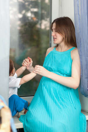 windowsill: Pregnant woman wearing long blue dress plays with little boy sitting on the window-sill