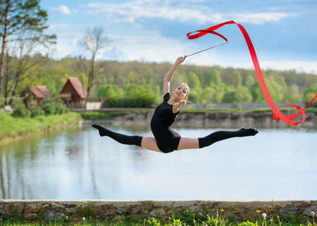 Young rhythmic gymnast doing split jump during ribbon exercises. Фото со стока
