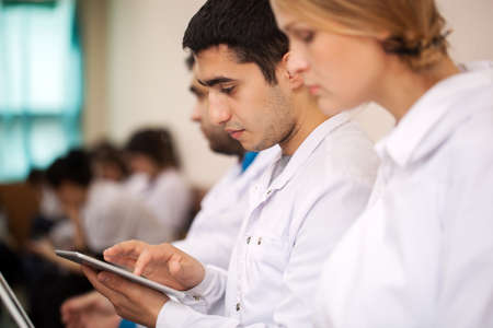 Medical student or young doctor using tablet computer during lecture, conference or symposium