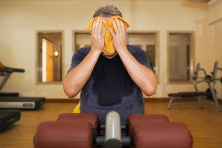 hombres maduros: El hombre en el gimnasio después del entrenamiento. Él es sudoroso, agotado y limpiándose la cara con una toalla