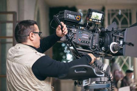 Operador de la cámara con equipo profesional moderno de trabajo durante la grabación de la película
