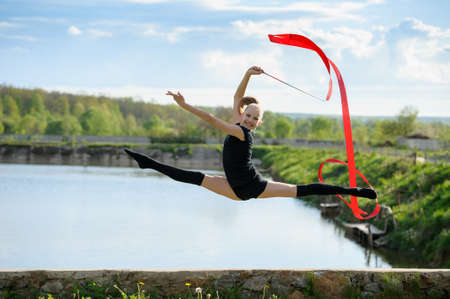 Rhythmic gymnast girl performing with a red ribbon outdoor. Leg-split in a jump against rural nature background