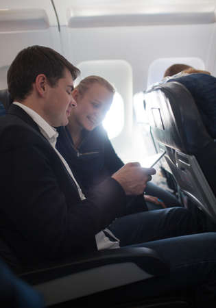 illuminator: Young businessman showing something to the woman on smartphone while they traveling by plane. Bright sunlight coming through the illuminator