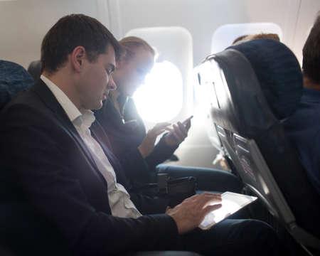 비행 중 스마트 폰을 사용하여 디지털 태블릿와 여자 근무하는 젊은 사업가. 비행기 창에서 밝은 햇빛