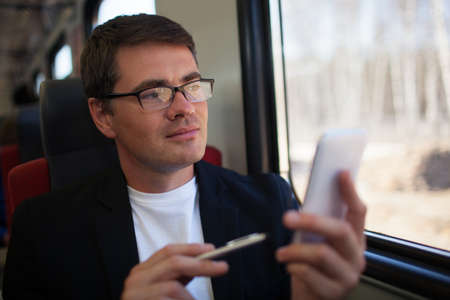 travel phone: Young businessman traveling by train. He using smart phone and looking out the window. The way reflecting in his glasses Stock Photo