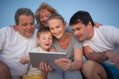 Happy big family having good time together. Grandparents and parents looking at the pad screen while boy using it