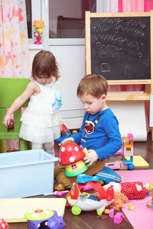 small girl: Little boy and girl playing at home. They surrounded with toys on the floor. Easel with children scribble in background. Home activities
