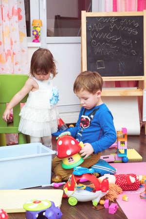 niño y niña: Niño y niña jugando en casa. Rodearon con los juguetes en el suelo. Caballete con niños garabatos en el fondo. Actividades Inicio
