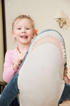 plushie: Little girl is playing with big plush shark. Stock Photo