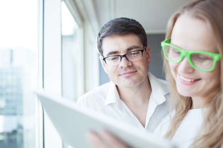 touch pad: Happy young businessman and businesswoman in glasses using touch pad by the window in light office