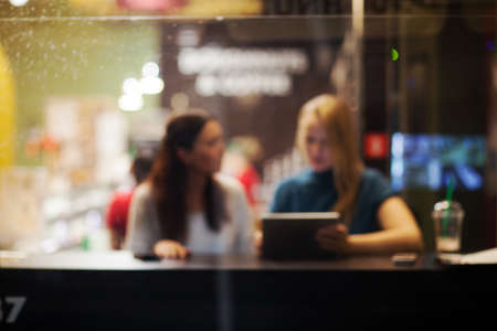 tab: Defocused shot of two women friends sitting in the cafe and using touch pad. View through the glass. Leisure time