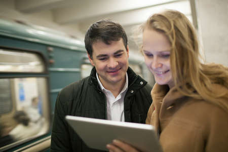 tab: Happy young couple watching something on tablet computer in underground. Train passing by