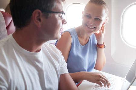 Felices los jóvenes que viajan en avión. Mujer que habla con un hombre, mientras que usando la computadora portátil. La luz del sol brillante en las ventanas de avión