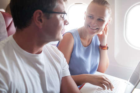 Happy young people traveling by plane.  Woman talking to a man while using laptop. Bright sunlight in airplane windows Stock Photo