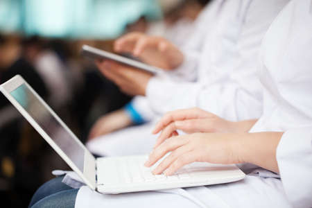 Woman and man doctors or medical students on the lecture or symposium. They using laptop and digital tablet. Focus on female hands typing on portable personal computer