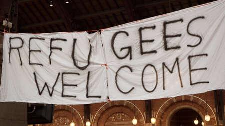 Handgemaakte banner Vluchtelingen Welkom wordt opgehangen in Kopenhagen station door de plaats waar de lokale bevolking te brengen kleding voor vluchtelingen.