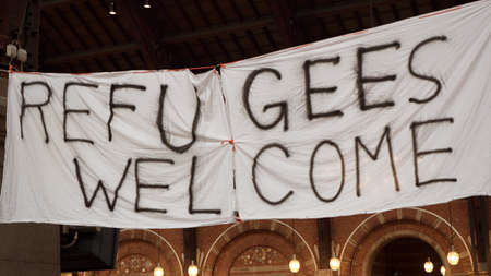 Handmade banner Refugees Welcome is hanged in Copenhagen railroad station by the place where locals bring clothes for refugees.