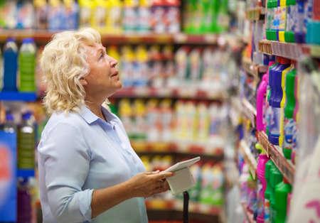 gospodarstwo domowe: Starszy kobieta z komputera typu tablet w sklepie. Ona patrzy na detergenty w dziale chemii gospodarczej