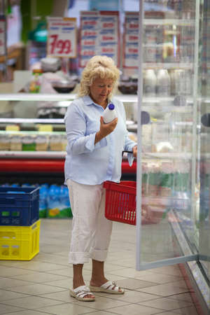 food products: Senior woman shopping for food in the grocery store. She taking bottle of milk from the fridge and checking the label before putting it into the basket Stock Photo