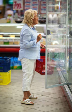 produce departments: Senior woman looking at the dairy in open fridge in the supermarket. Great assortment of products making her think what to choose