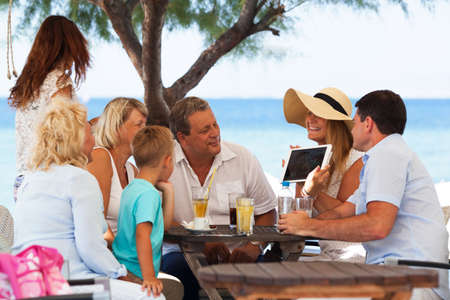 Big cheerful family with child looking at photo on tablet computer. They sitting in outdoor cafe on tropical beach. Vacation memories