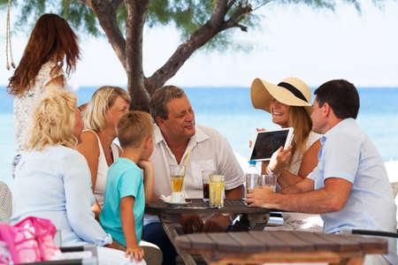 태블릿 컴퓨터에서 사진을보고 아이 함께 큰 쾌활 한 가족. 그들은 야외 카페에서 열 대 해변에 앉아. 휴가 추억