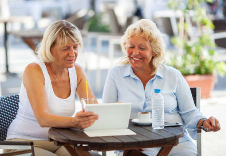women friends: Cheerful senior women with touch pad enjoying sunny day in outdoor cafe. They looking at tablet screen and smiling Stock Photo