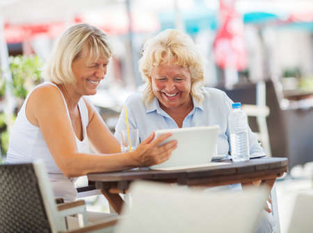 enjoyable: Senior women in outdoor cafe on sunny summer day. They looking at pad screen and laughing. Enjoyable time with friend and tablet PC
