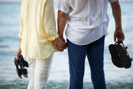 Man and woman standing barefoot by the sea and holding hands. Romantic vacation 写真素材