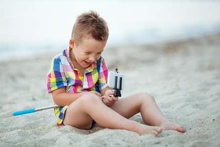 Piccolo ragazzo che ride divertendosi con smart phone e selfie bastone sulla spiaggia