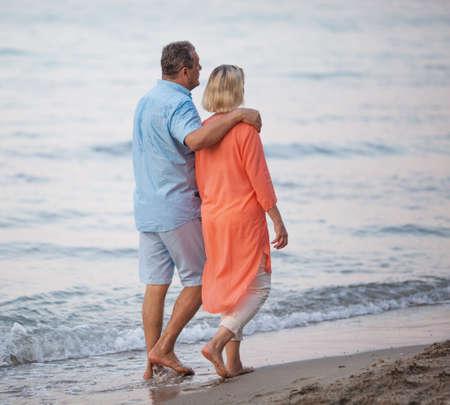 enjoyable: Senior couple walking together along the coast. Man embracing the woman while they having enjoyable barefoot outing on the beach Stock Photo
