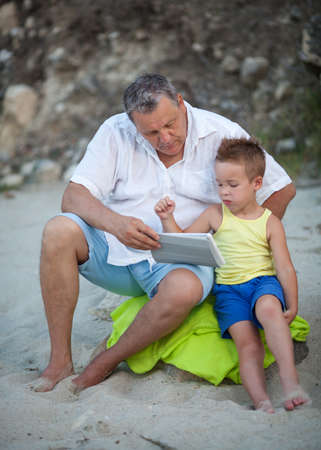 they are watching: Grandfather and grandson spending time on the beach. Man watching the boy using tablet computer, they sitting on green blanket
