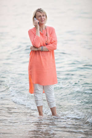 woman foot: Senior blond woman having a phone conversation standing barefoot in sea water at sunset