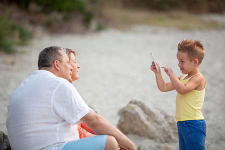 family beach: Smiling little child with smart phone taking picture of happy grandmother and grandfather. Family leisure outdoor Stock Photo