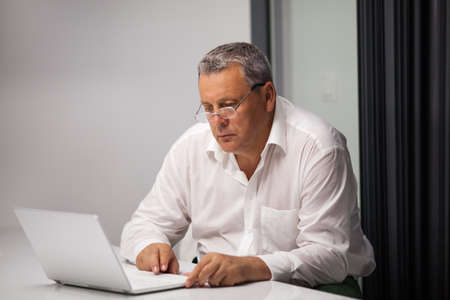office use: Mature serious businessman in white shirt and glasses deep at work with laptop in office Stock Photo