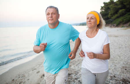 regular people: Senior man and woman having a run along the shore. Scene with sea, sand and trees. Healthy and active way of life