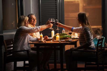 famiglia: Cena di famiglia all'aperto nel cortile in serata tranquilla. Giovane donna e genitori anziani tostatura con vino mentre bambino che gioca i giochi