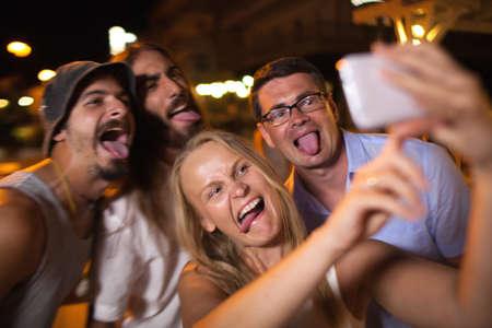 tonto: amigos jóvenes con las caras divertidas que hacen autofoto teléfono inteligente en la noche. Ellos engañan y poner hacia fuera las lengüetas Foto de archivo