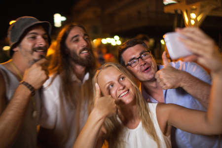 thumbsup: Group of happy and excited young people having good time outdoor at night. Focus on man and woman showing thumbs-up and making mobile phone selfie