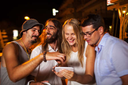 watch video: Young happy friends outdoor at night. They look at photos they made with smart phone. They laughing and getting excited