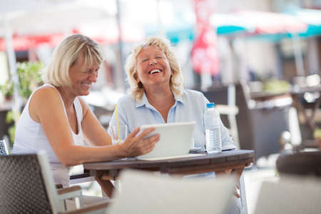 enjoyable: Two female friends using touch pad in street cafe and laughing. Senior women spending enjoyable summer day