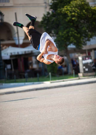 somersault: Young sportsman performing his acrobatic skills in doing somersault. Show in the city street