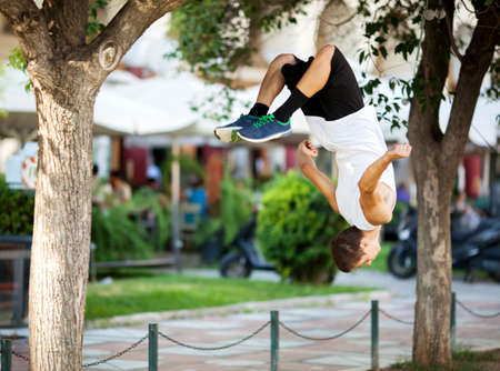 tumble down: Young extreme athlete doing front flip between the trees. City street with outdoor cafe in background