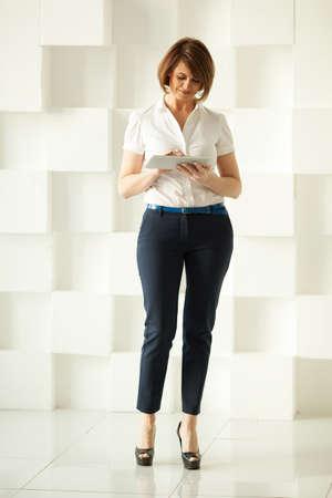 pantalones abajo: La sonrisa de negocios de pie contra la pared blanca mientras mira la tablilla en la mano