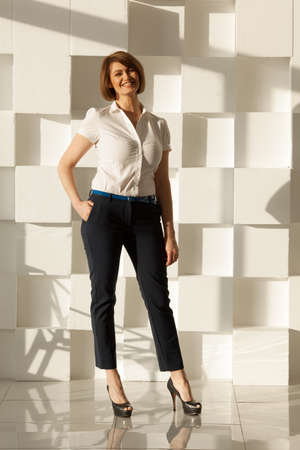 confident business woman: Smiling businesswoman in high heel shoes looking at camera while holding hand in pocket. Modern white wall on background