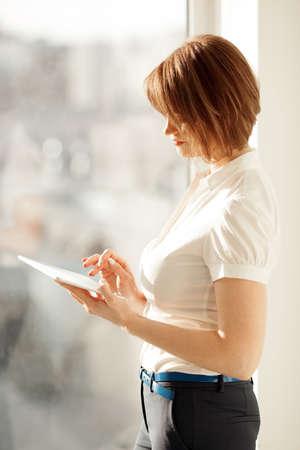 pantalones abajo: Vista lateral de la mujer que trabaja en la tablilla cerca de la ventana en la luz del sol
